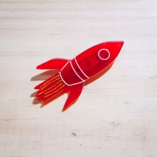 Red retro rocket brooch against a wood grained background