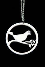 Bird on a branch pendant hanging from a silver plated chain