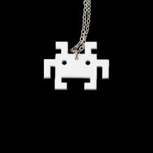 White laser cut space invader bot - a close up on a black background